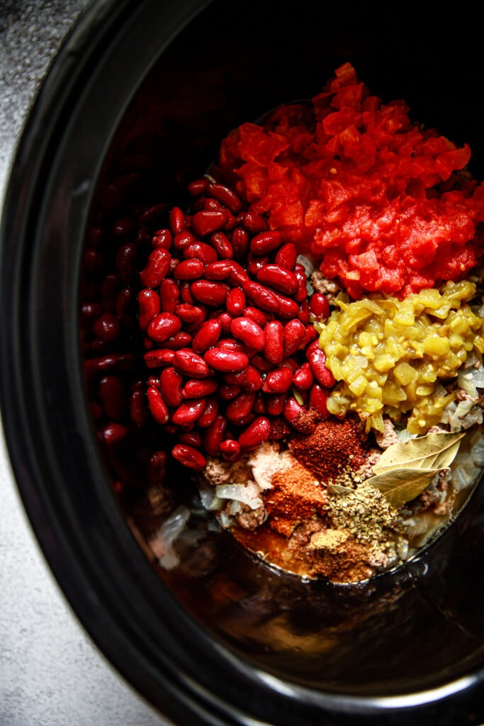 chili ingredients in a black slow cooker