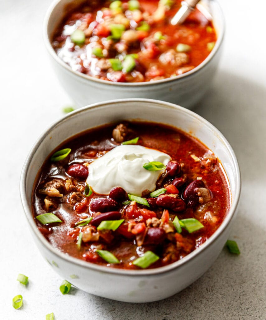 chili in a bowl topped with sour cream and green onions