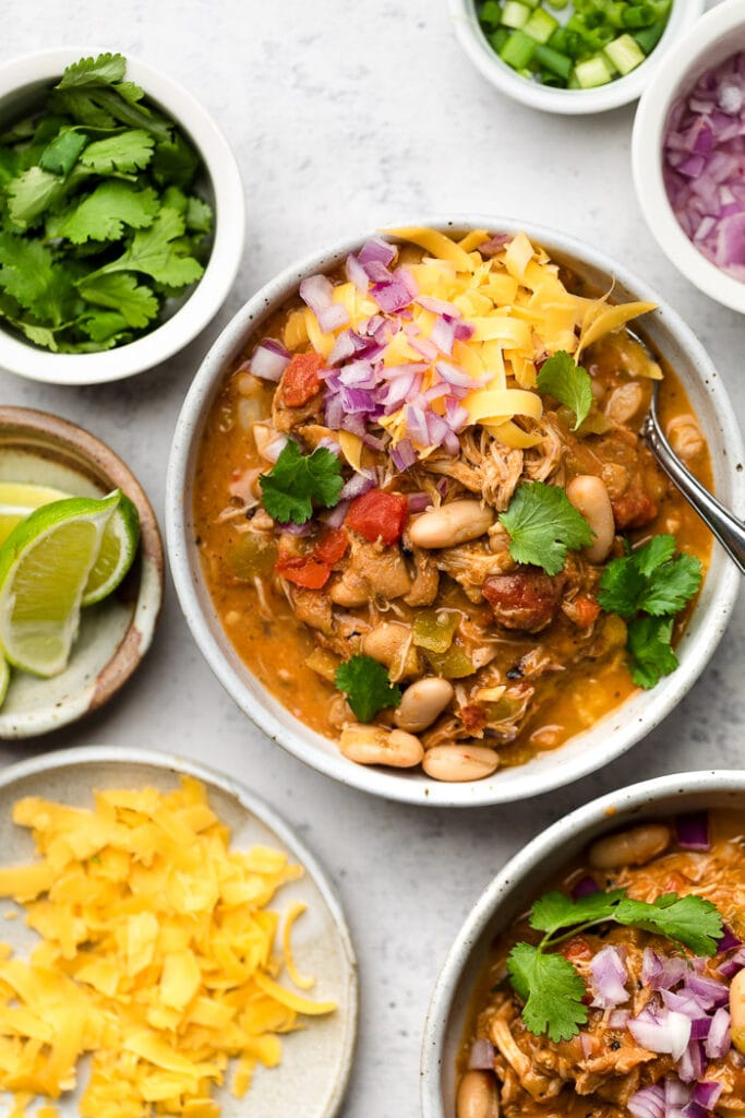 chicken chili in a white bowl with toppings