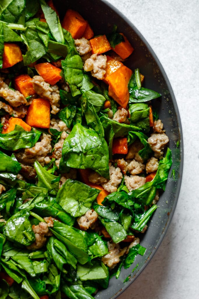 spinach, sausage, and sweet potatoes in a non-stick pan
