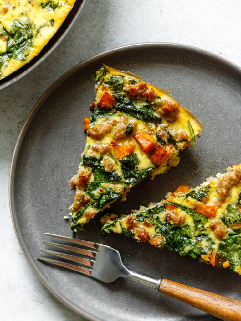 two slices of frittata on a grey plate with a fork