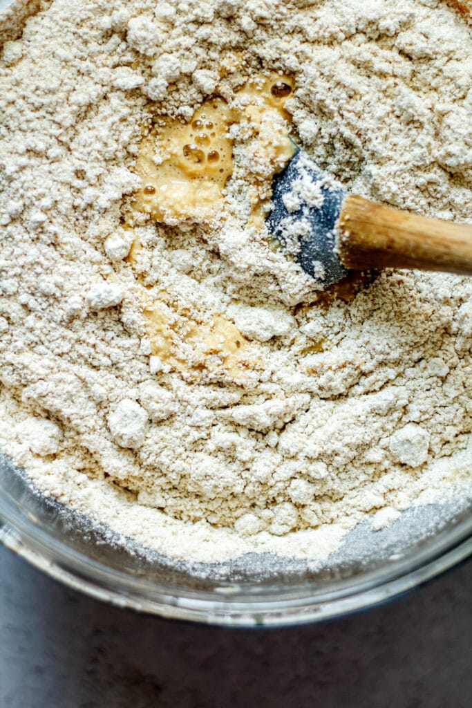 oat flour in the banana batter with spatula in clear glass bowl