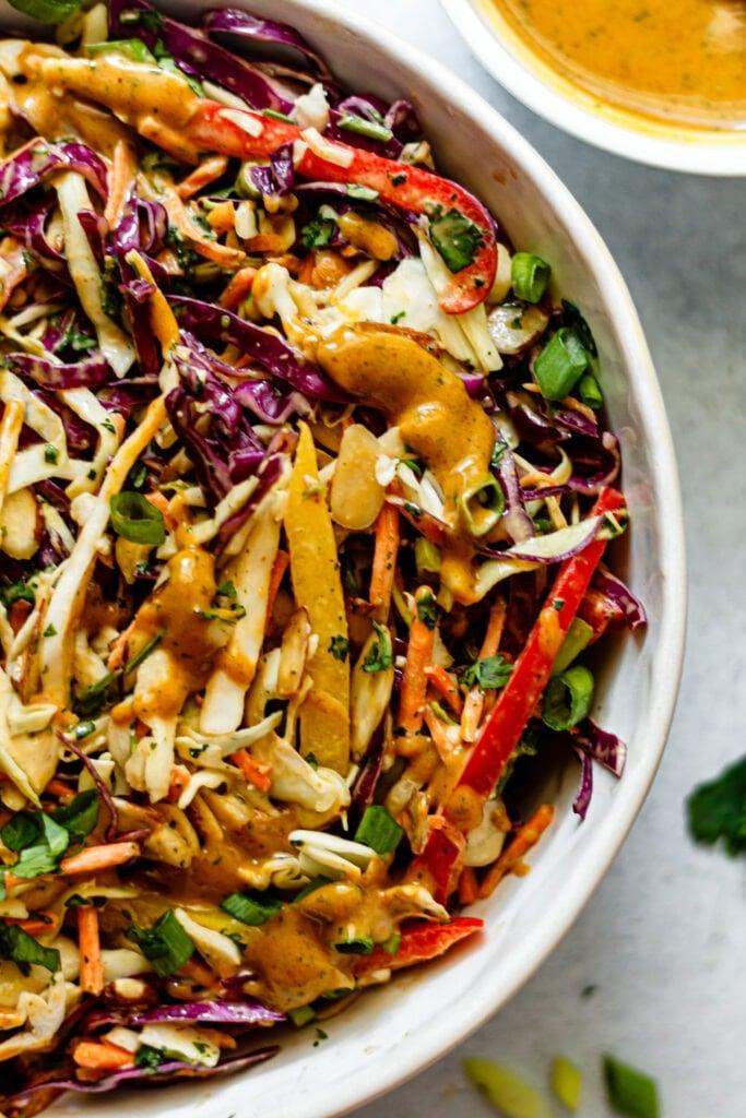 thai crunch salad in a white bowl on grey background