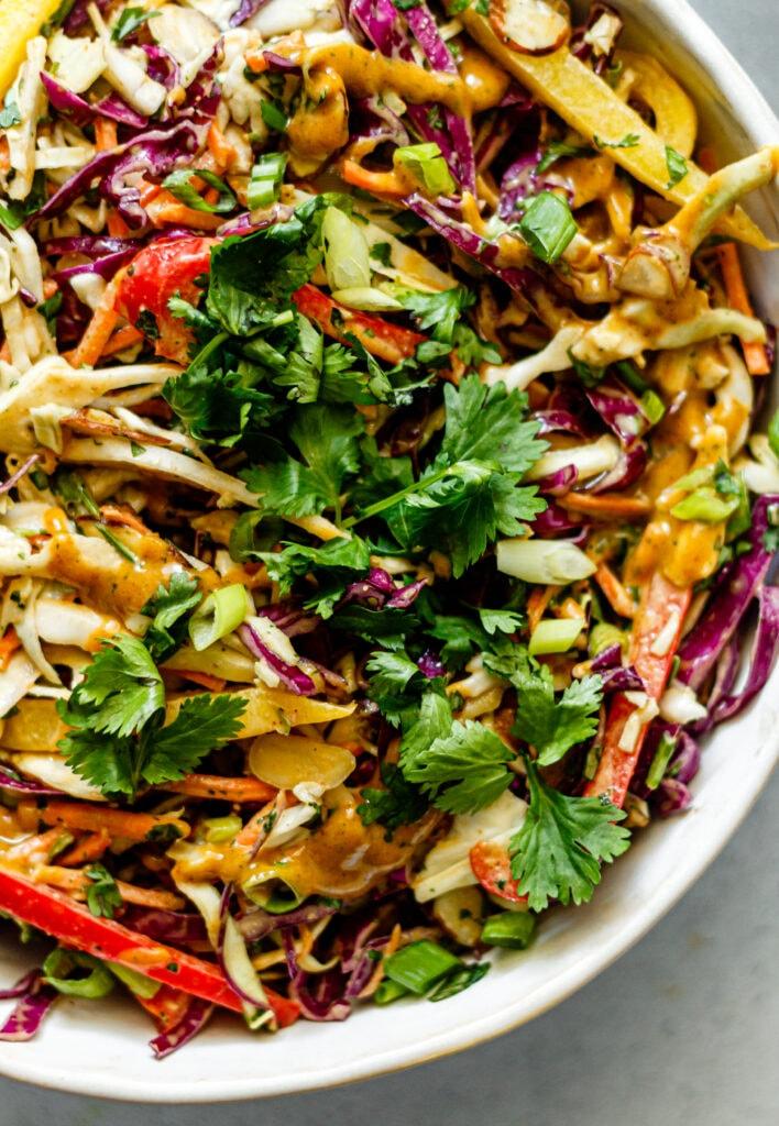 Thai crunch salad in white bowl on grey background