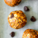 energy bites on a parchment paper surrounded by chocolate chips