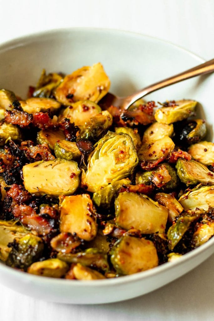 Roasted Brussels sprouts in a white bowl with gold spoon