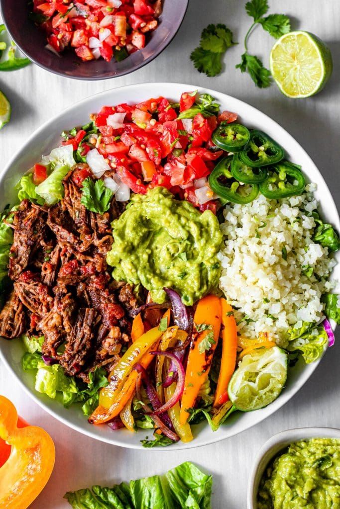 slow cooker chipotle beef burritos in a white bowl with veggies scattered around