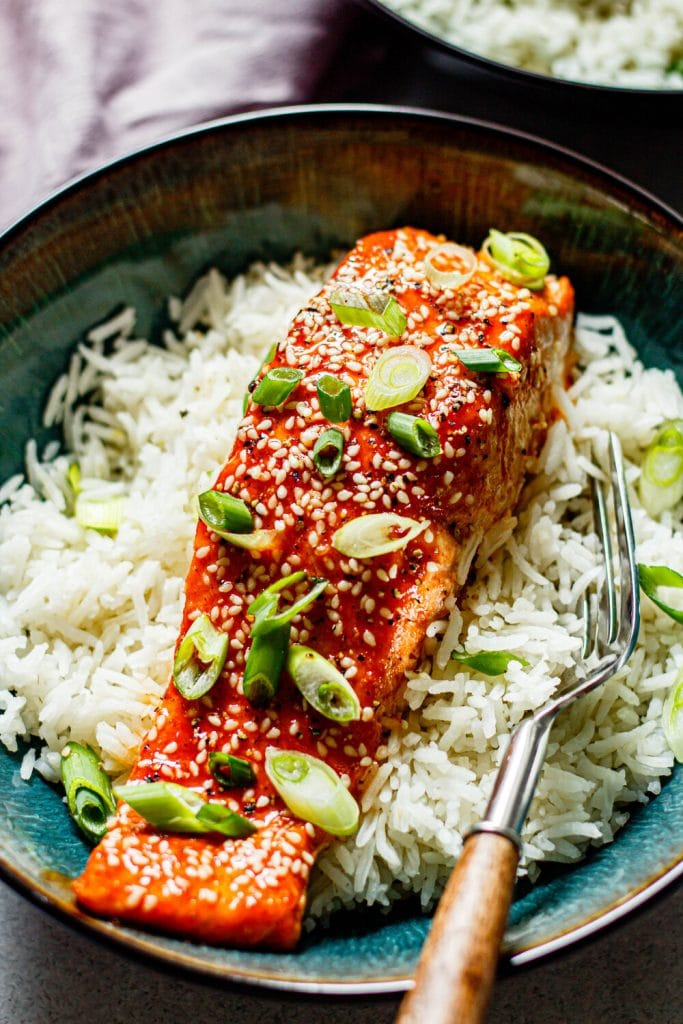 honey sriracha salmon on white rice in a bowl with a fork on the side
