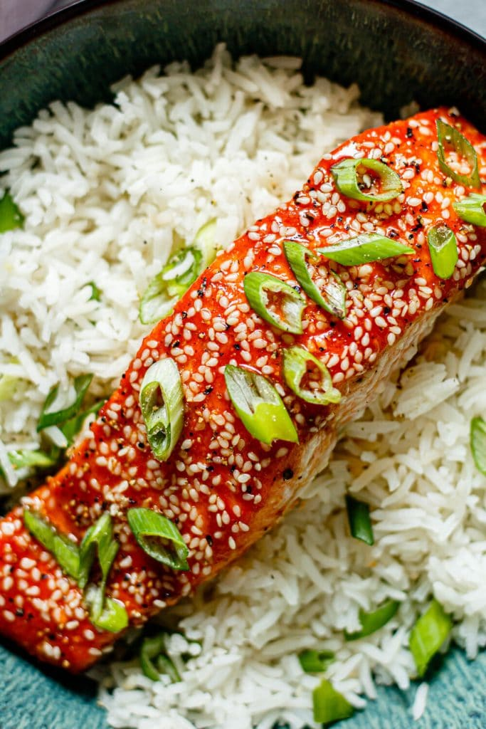 honey sriracha salmon over white rice with green onions on top