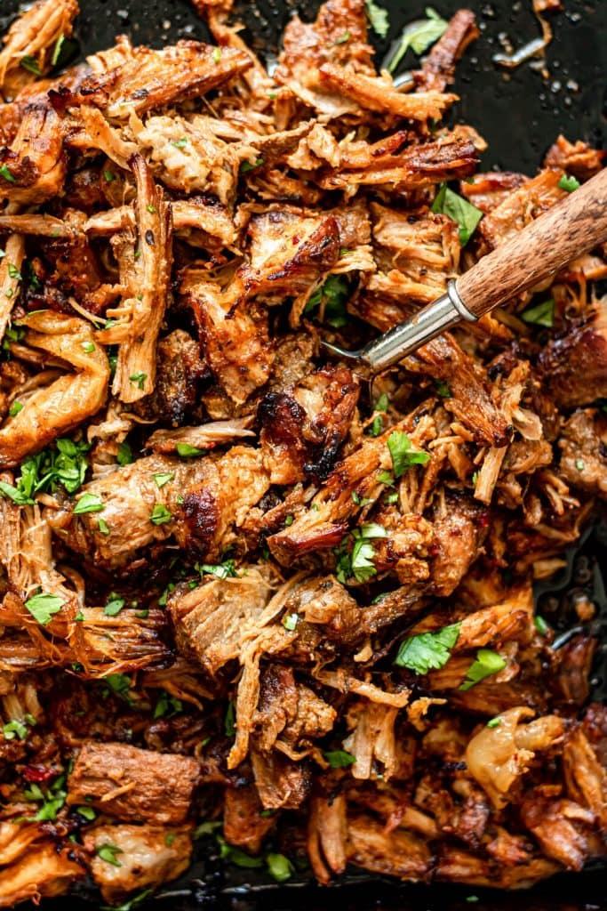 crispy pork carnitas on a sheet pan with fork
