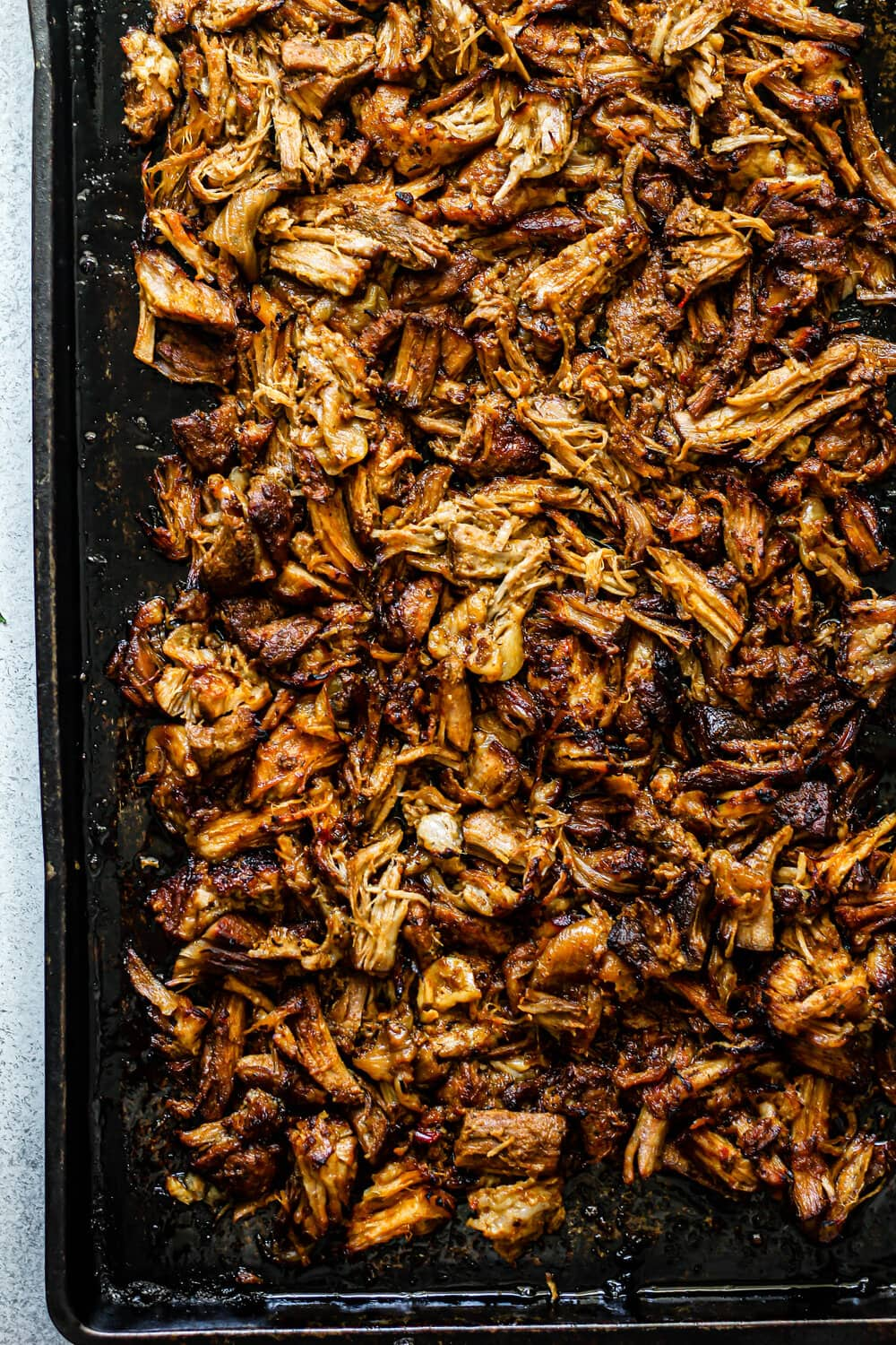 Crispy Pork Carnitas on dark sheet pan