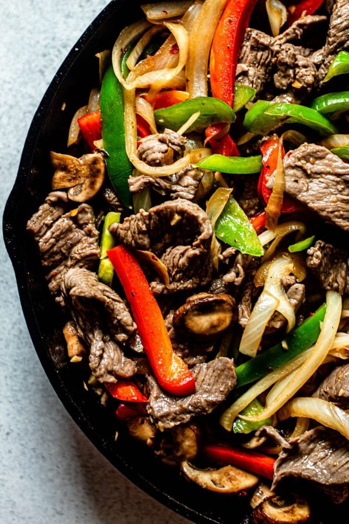 steak and peppers in a cast iron skillet