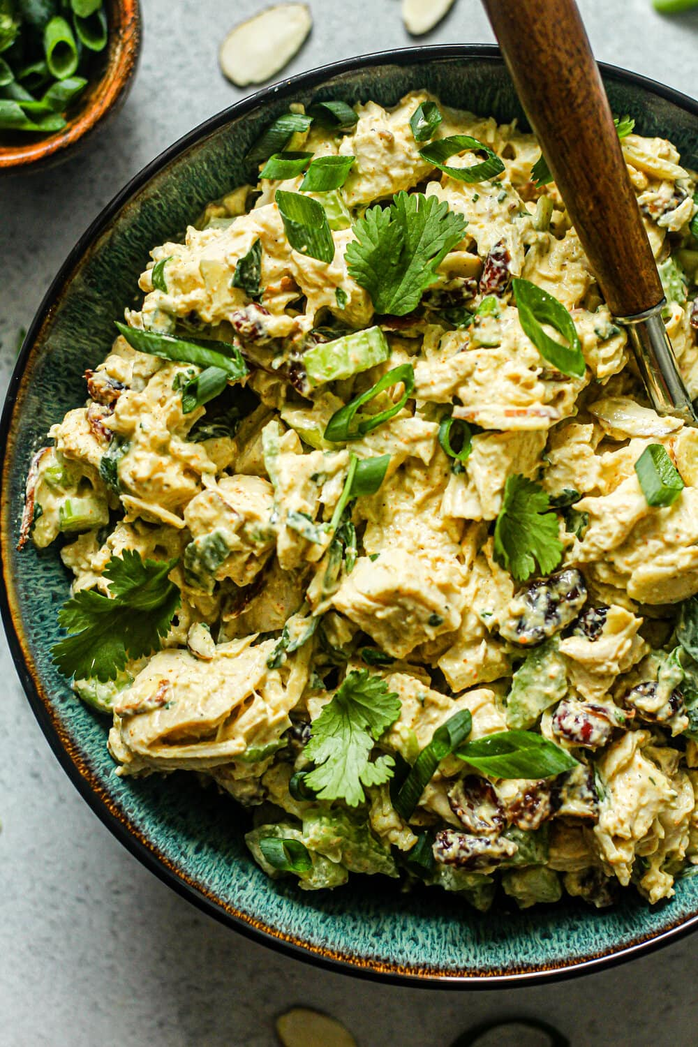 Curry Chicken Salad in a blue bowl with brown fork