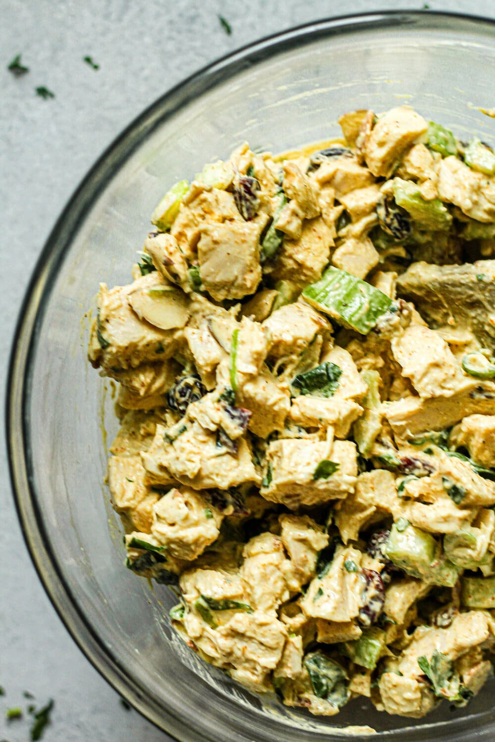 Curry Chicken Salad ingredients stirred together in glass mixing bowl