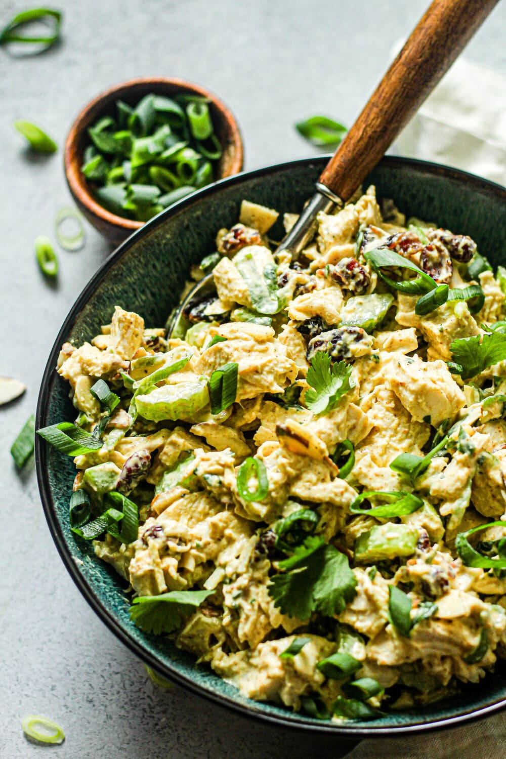 Curry Chicken Salad in a blue bowl with green onions in the background