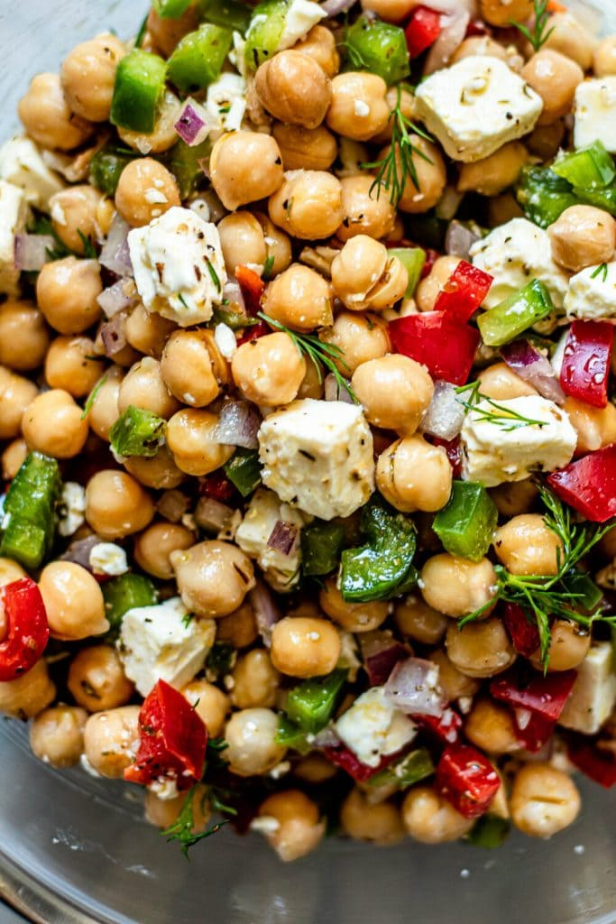 Greek chickpea salad in glass mixing bowl
