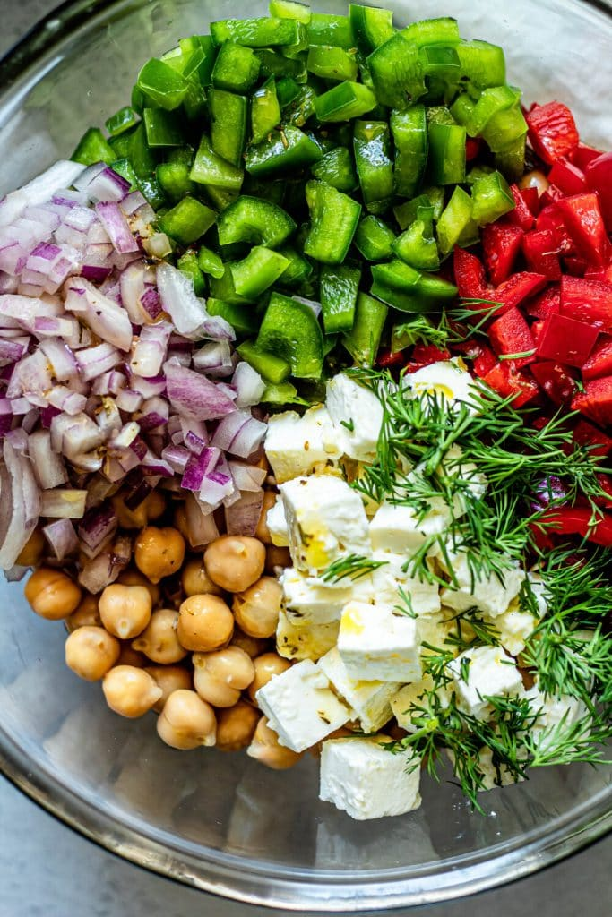chickpeas, red onion, green pepper, red pepper, feta cheese, and dill in a glass mixing bowl