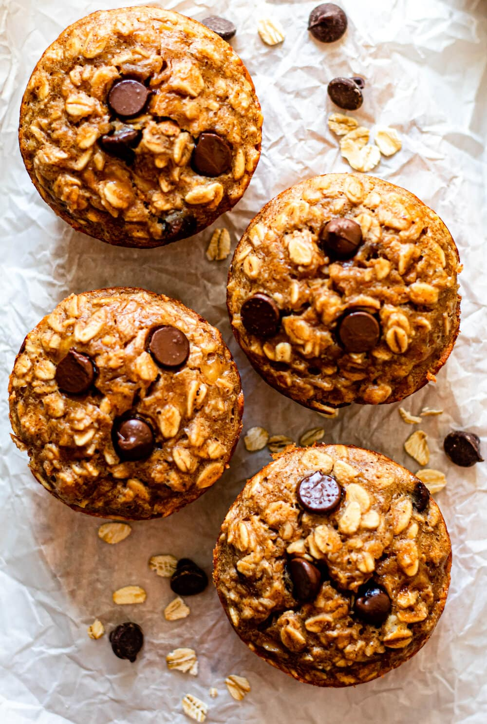 Four Peanut Butter Banana Baked Oatmeal Cups on white parchment paper with chocolate chips and oats scattered around