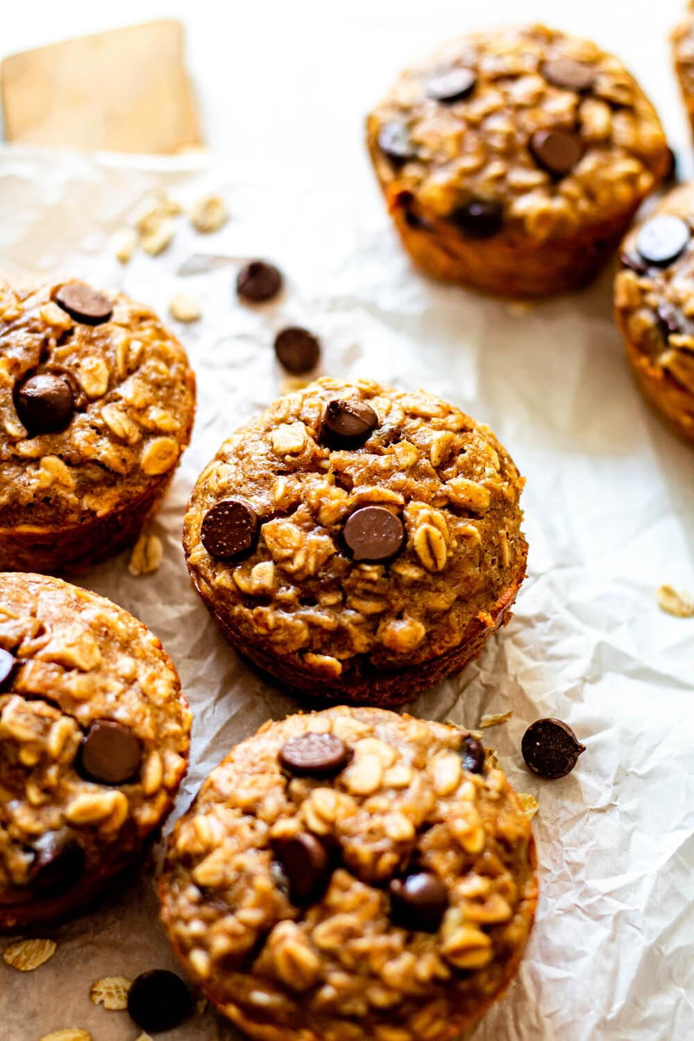 Peanut Butter Banana Baked Oatmeal Cups on white parchment paper with chocolate chips scattered around