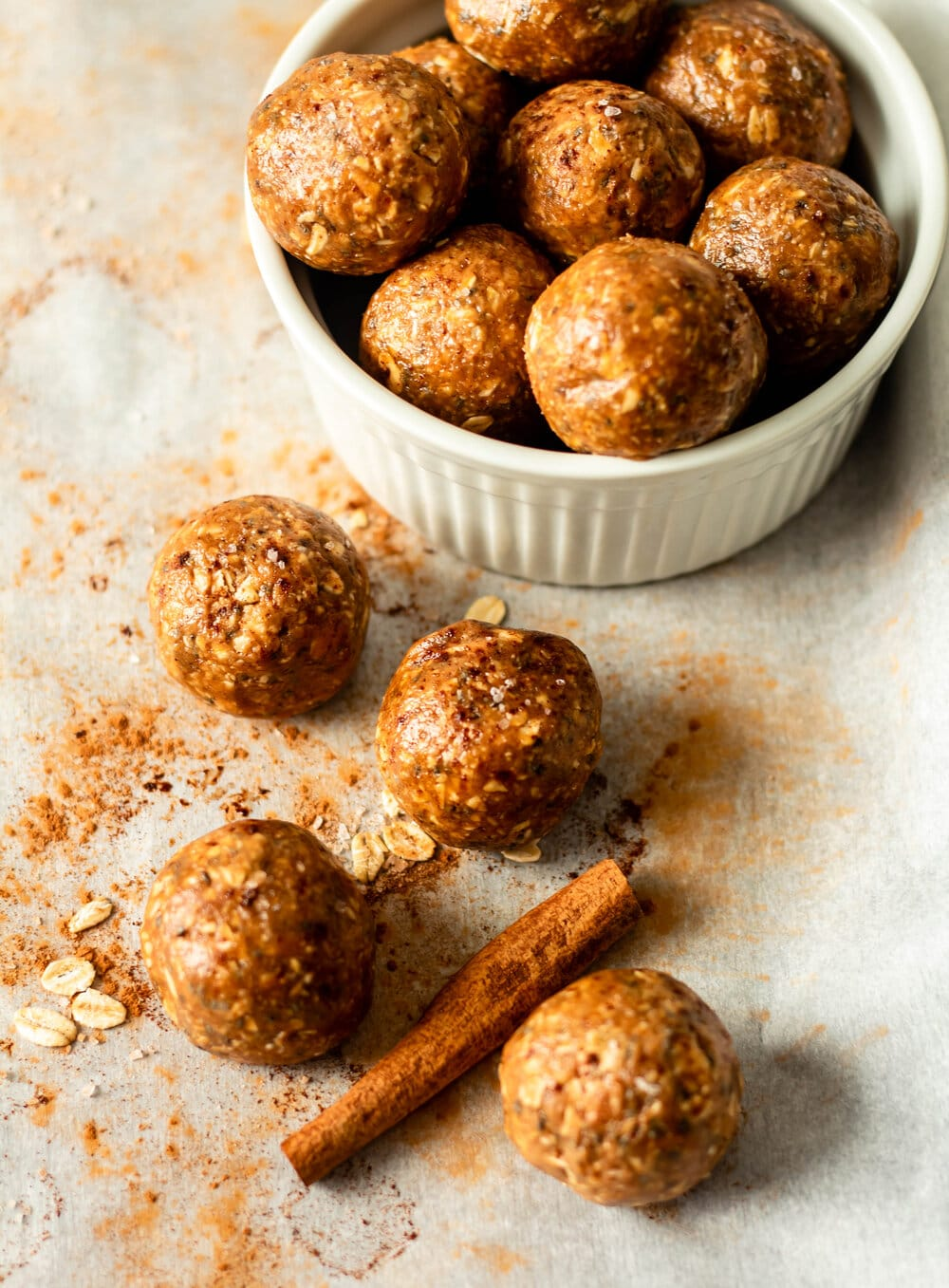 snickerdoodle energy bites in a white bowl with cinnamon stick on the side