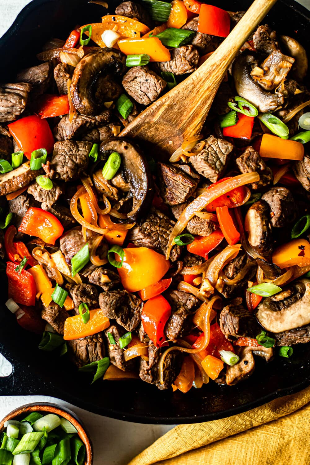 One Skillet Beef Tips with Peppers and Onions in a cast iron skillet with wooden serving spoon