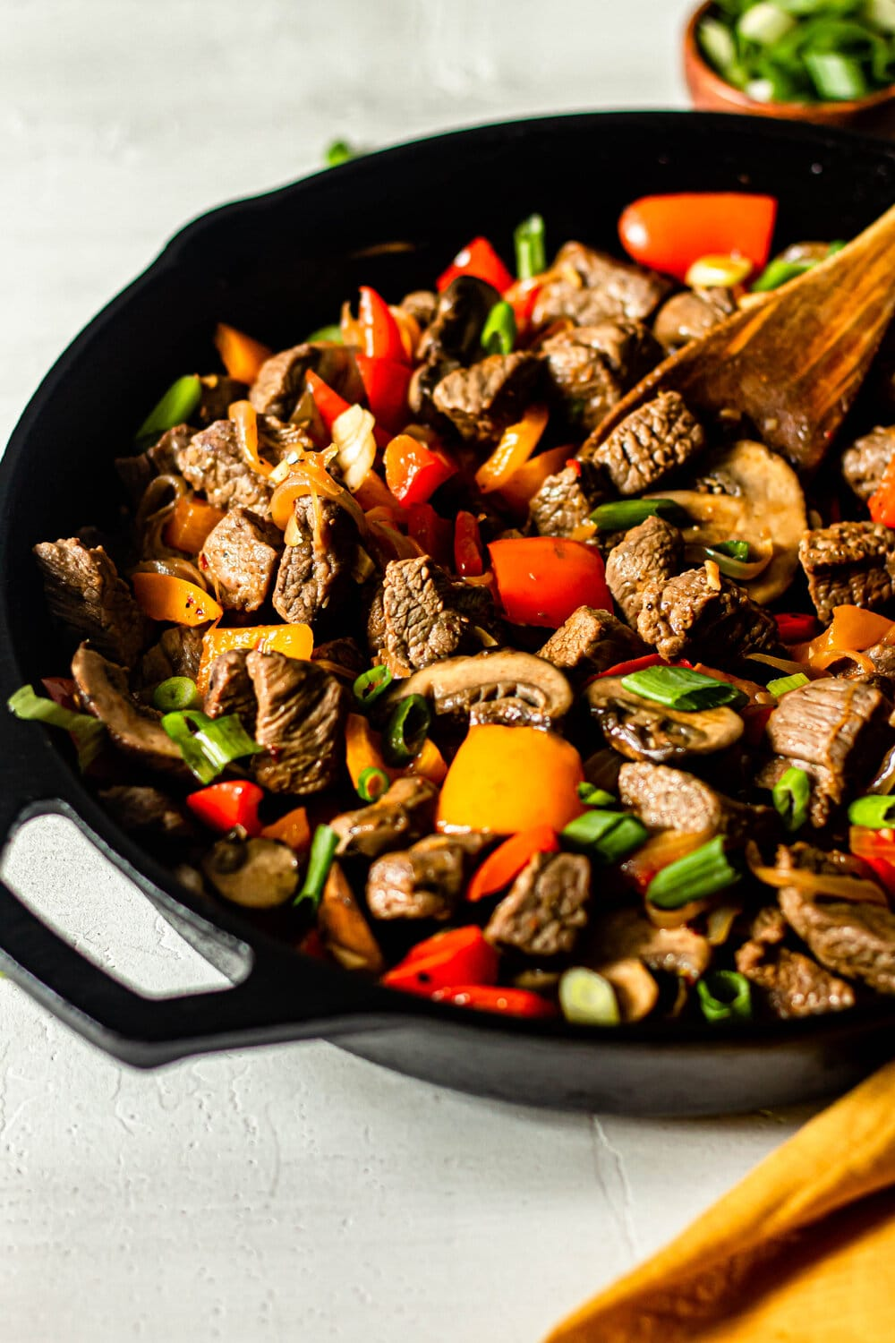 One Skillet Beef Tips with Peppers and Onions in cast iron skillet with wooden serving spoon