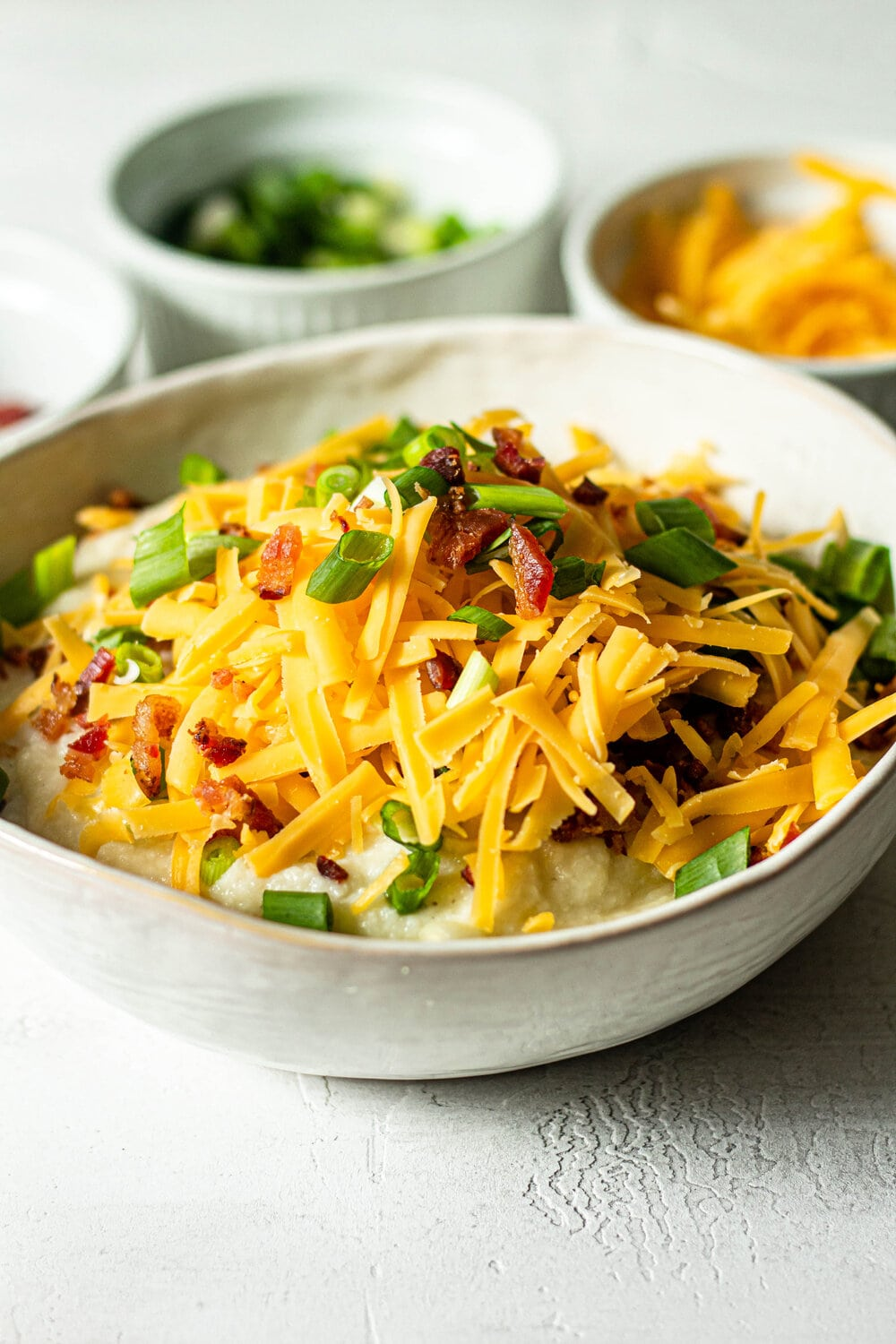 Loaded Mashed Cauliflower topped with cheese, green onions, and bacon
