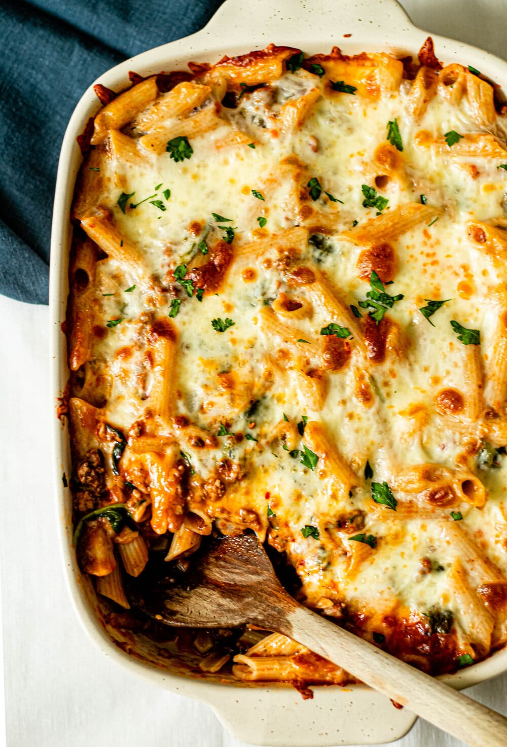 baked penne pasta in white baking dish with wooden serving spoon