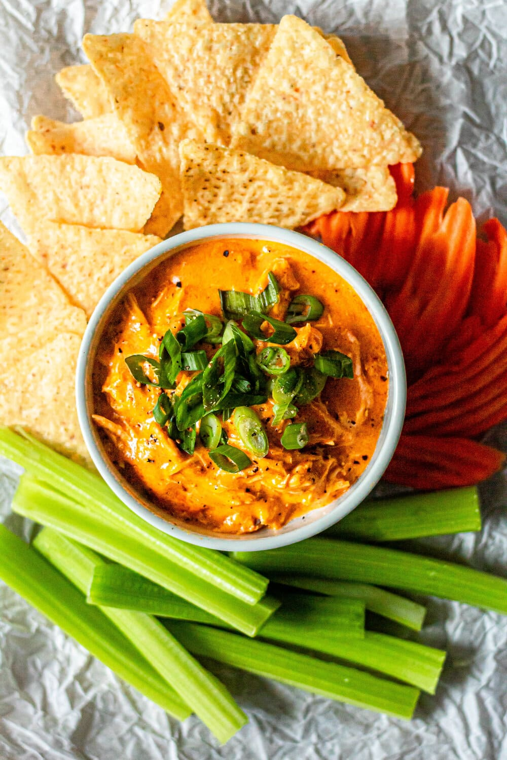 Dairy Free Buffalo Chicken Dip in white ramekin surrounded by tortilla chips, carrots, and celery