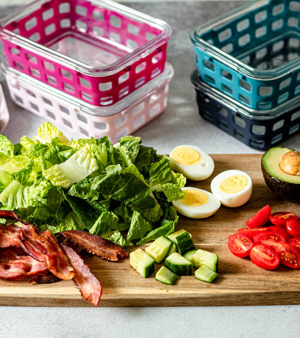 Easy Cobb Salad Meal Prep ingredients on a cutting board with meal prep containers in the background
