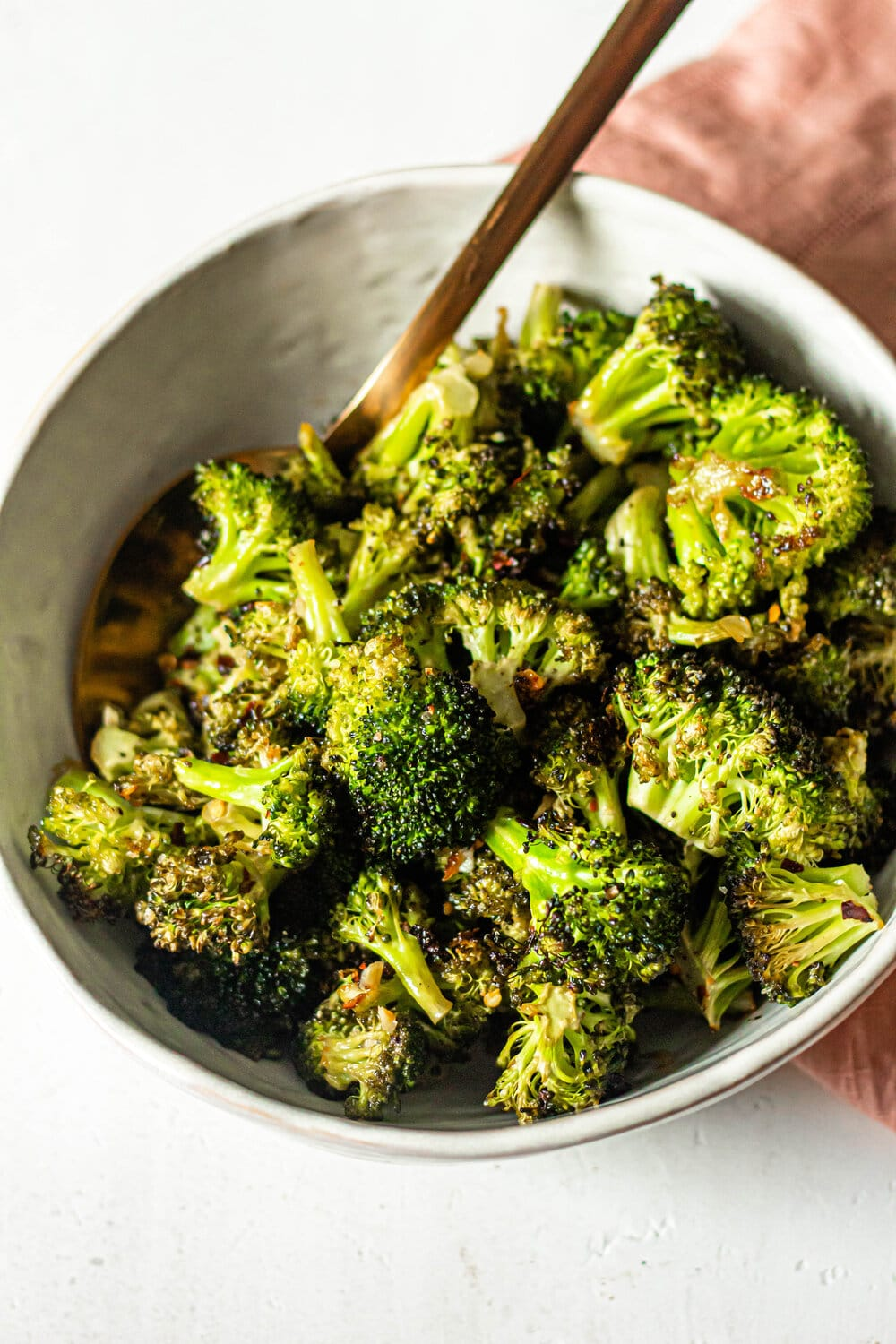 Roasted Garlic Lemon Broccoli in white bowl with gold spoon