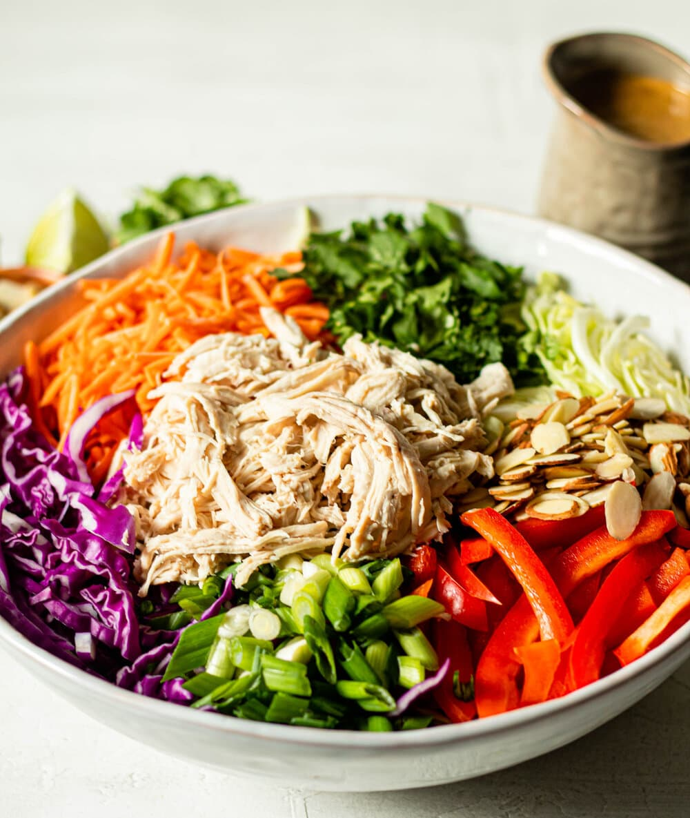 Chopped Thai Chicken Salad in white bowl with almond butter dressing in the background