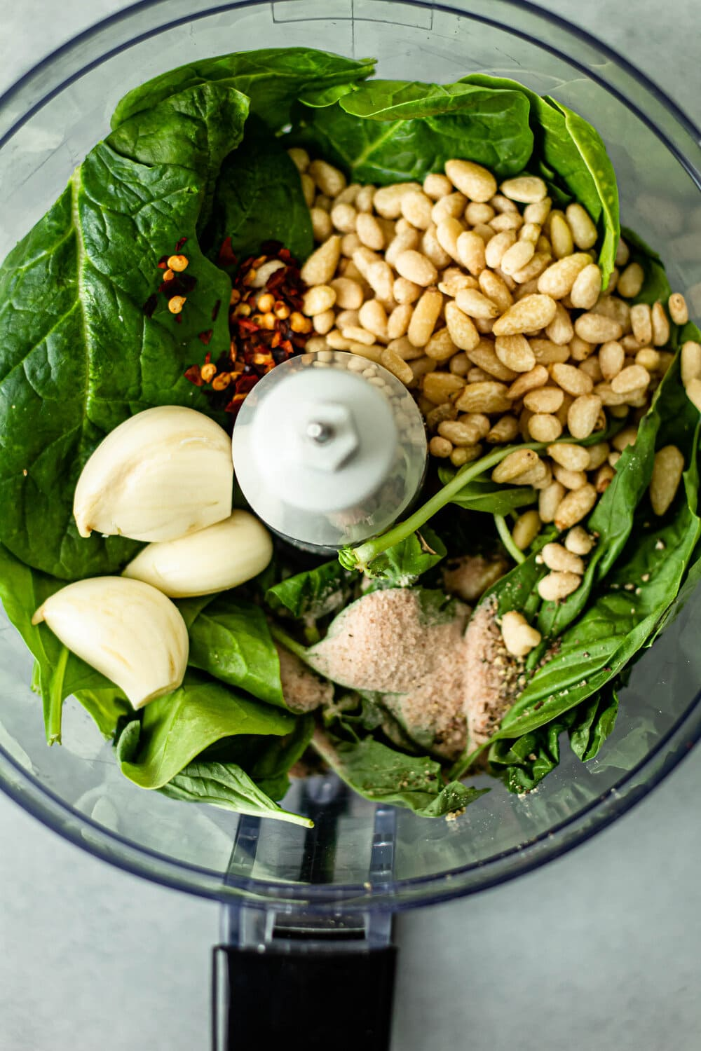 spinach, basil, pine nuts, red pepper flakes, salt and garlic in a food processor