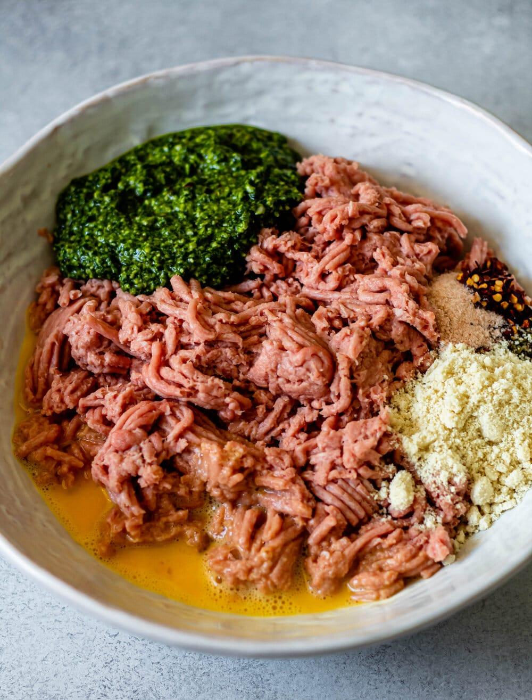 ground turkey, pesto almond flour, egg, and spices in white mixing bowl