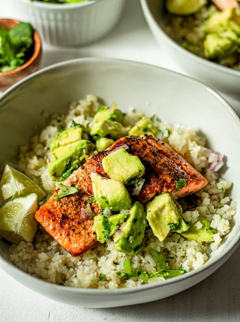 salmon with avocado salsa in a white bowl