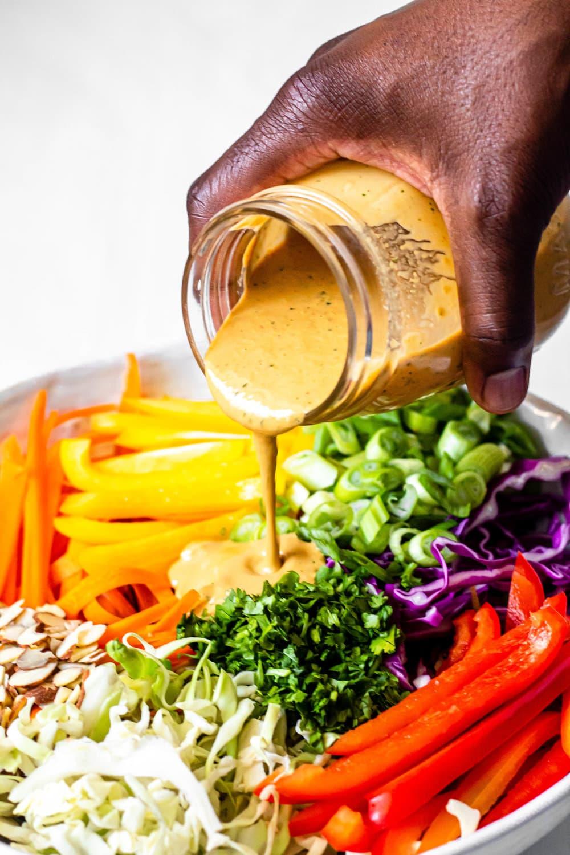Thai Crunch Salad with Creamy Peanut Dressing dressing poured on veggies