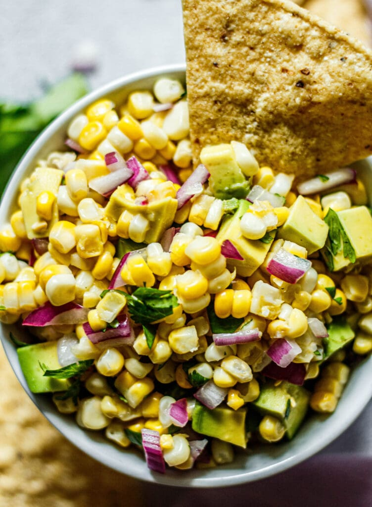 avocado corn salsa in a white bowl with tortilla chip dipped in the side of the salsa
