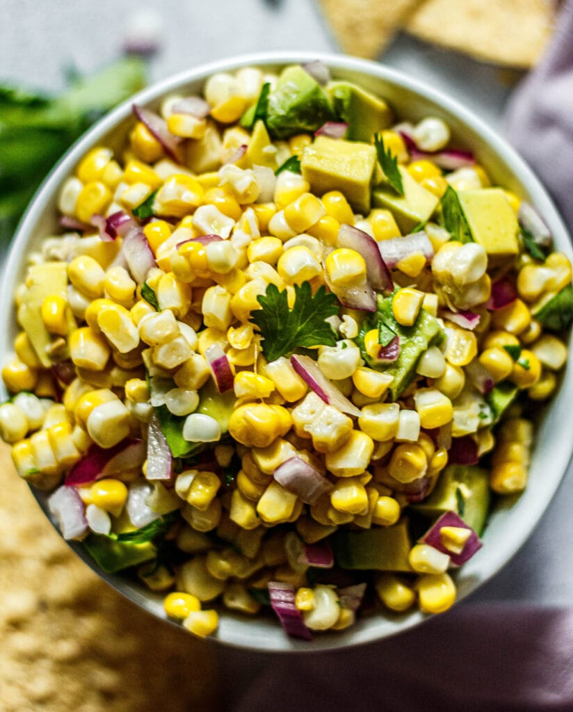 Avocado corn salsa in a white bowl with tortilla chips and cilantro sprinkled around the bowl