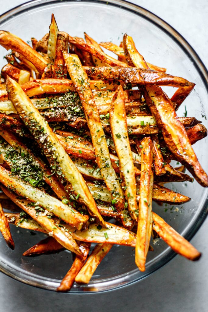 Air Fryer French fries in a clear mixing bowl seasoned with ranch seasoning