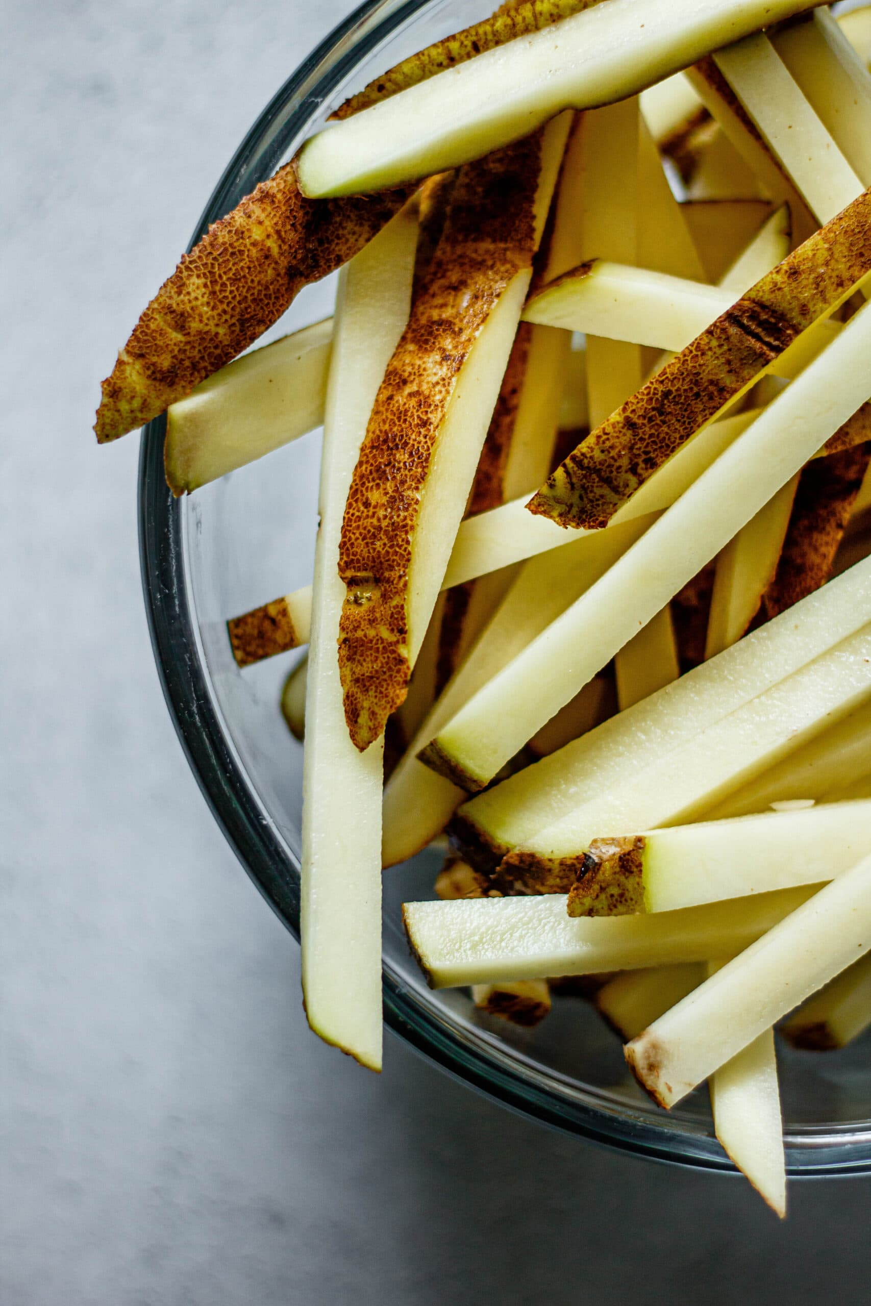 raw potatoes cut into French fries in glass mixing bowl