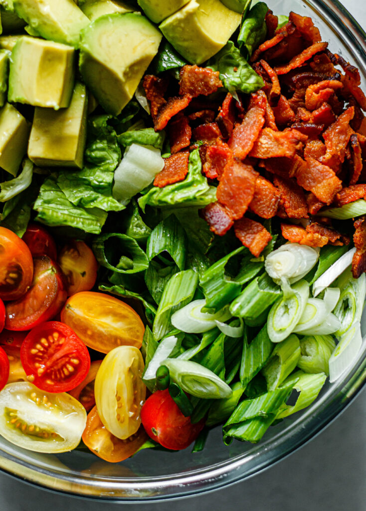 bacon, avocado, tomato, green onion, and romaine lettuce in glass mixing bowl