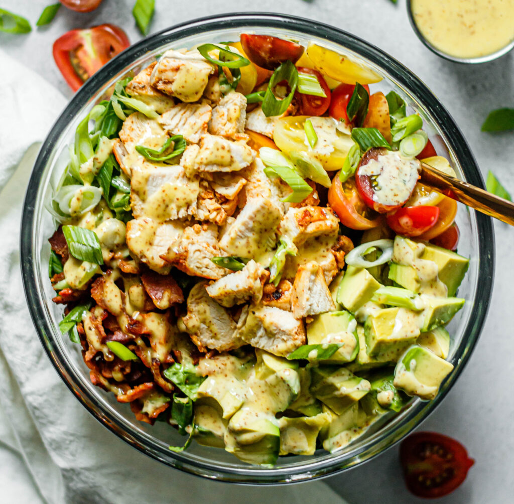 chicken, bacon, avocado, tomatoes, romaine lettuce, and green onions in a glass mixing bowl with honey mustard dressing