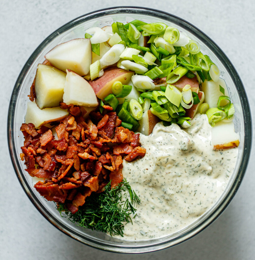 bacon, potatoes, green onion, dill, and ranch dressing in a glass mixing bowl