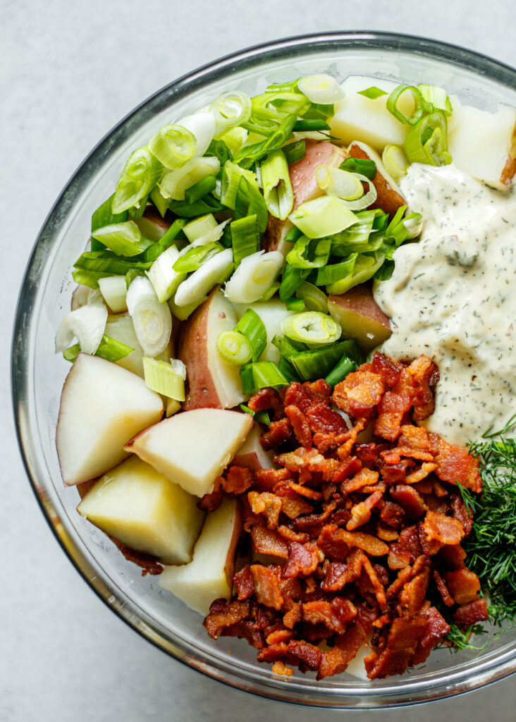 bacon, potatoes, green onion, ranch dressing in glass mixing bowl