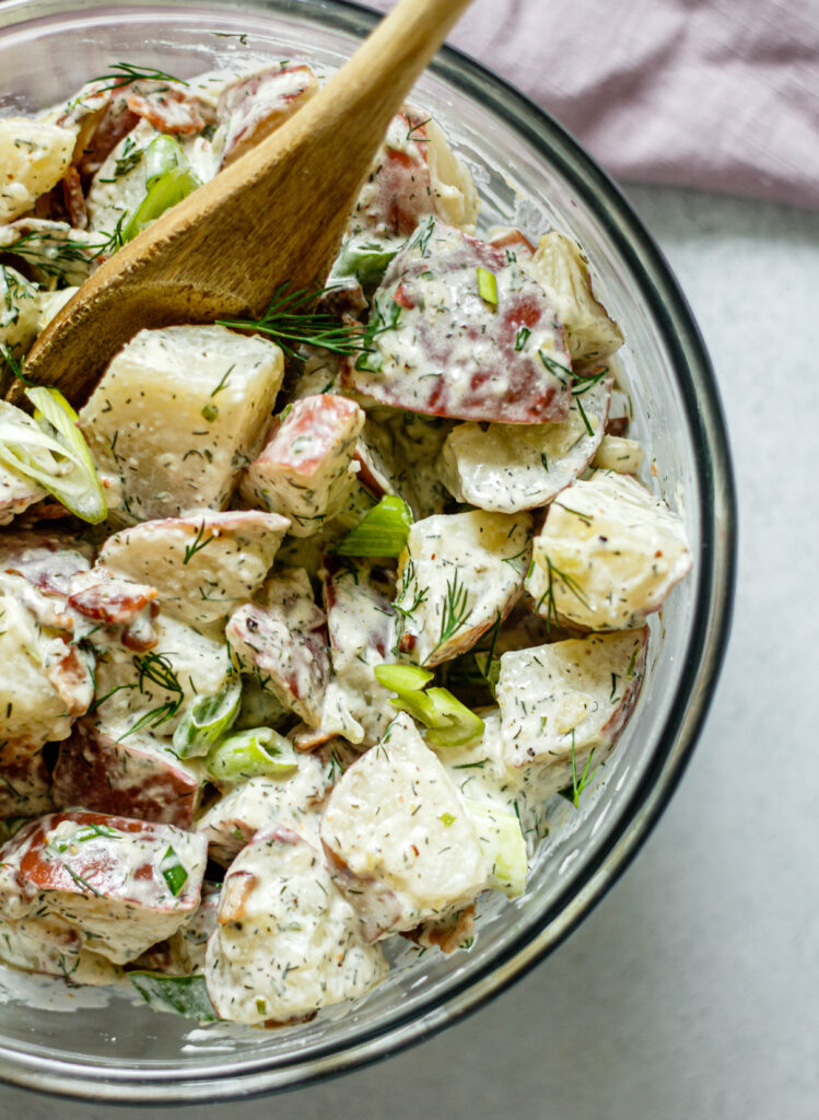 bacon ranch potato salad in a glass mixing bowl with a wooden spoon in the bowl