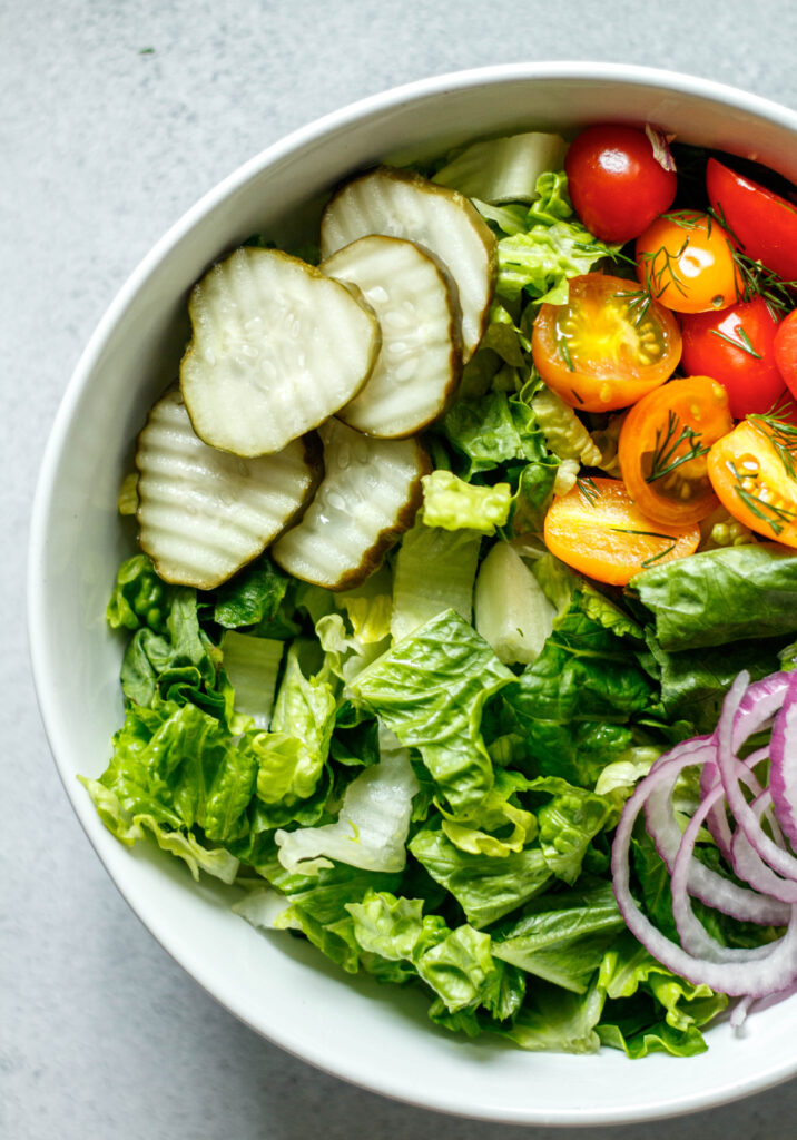 romaine lettuce, pickles, tomatoes, red onion in a white bowl