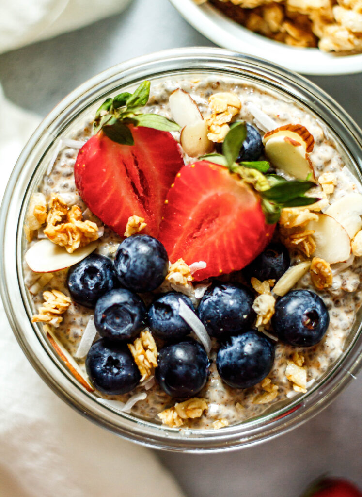 vanilla chia pudding topped with blueberries, strawberries, coconut, and granola