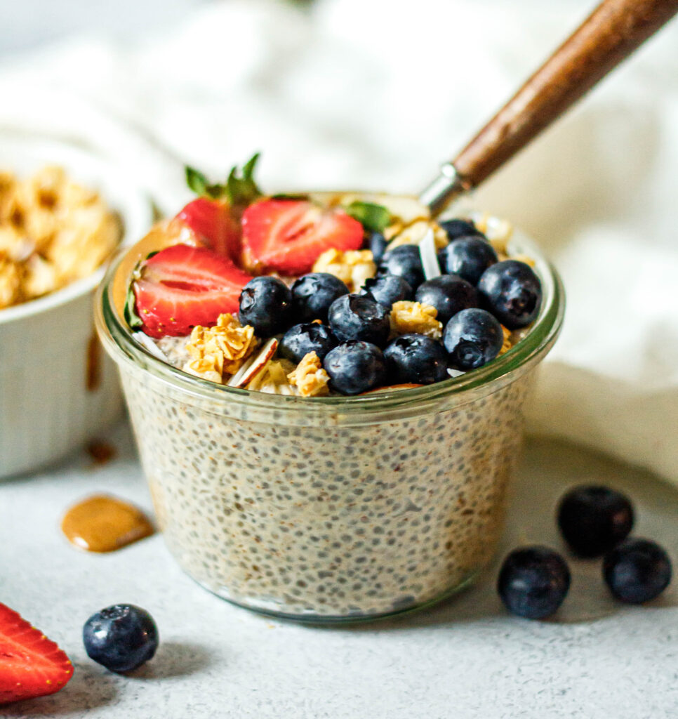 vanilla chia pudding in glass jar with strawberries, blueberries, coconut and granola on top