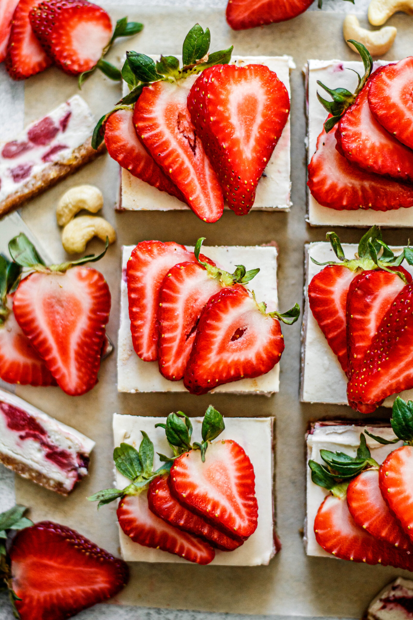no bake strawberry cheesecake bars on brown parchment paper with cashews and strawberries scattered around