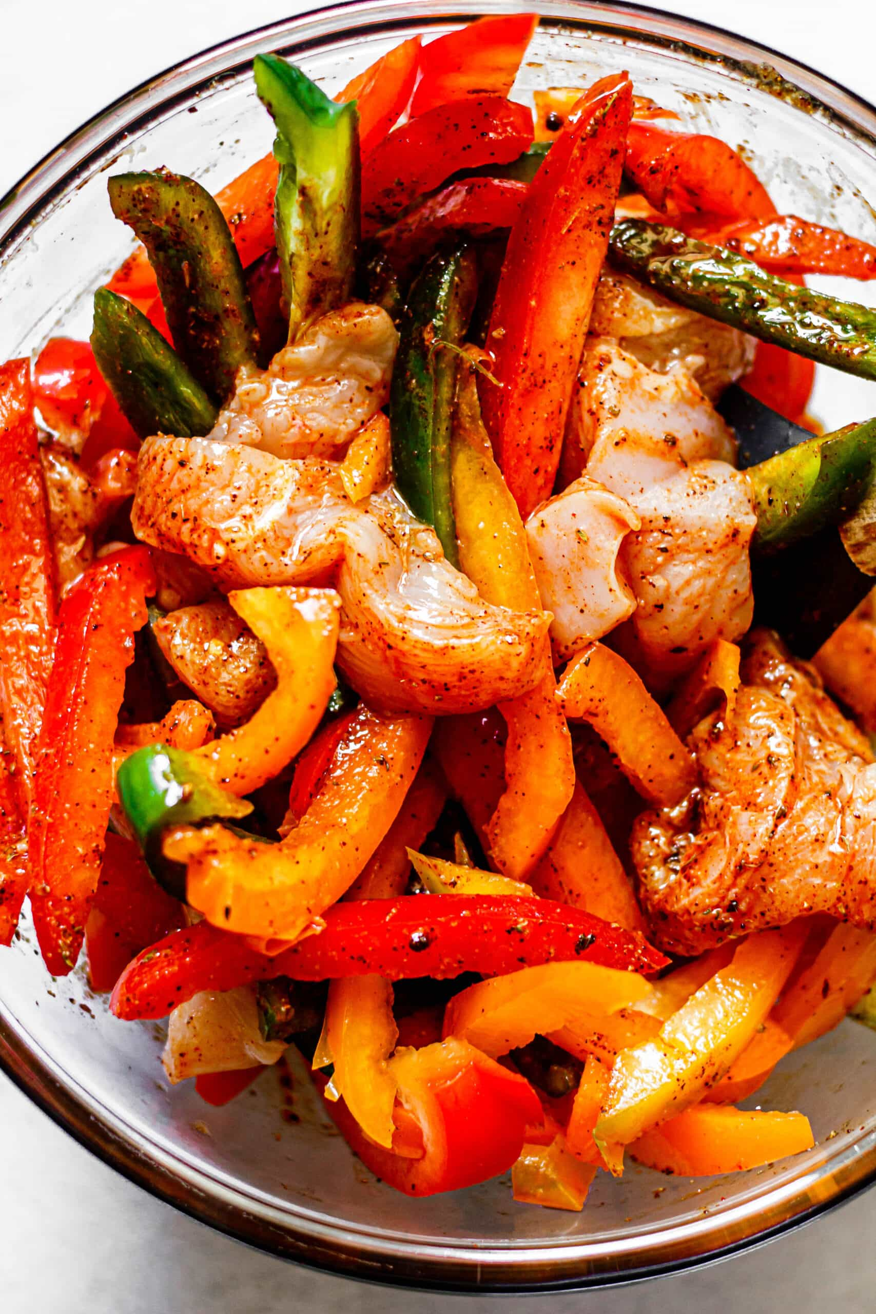marinade, chicken, and peppers tossed together in glass mixing bowl